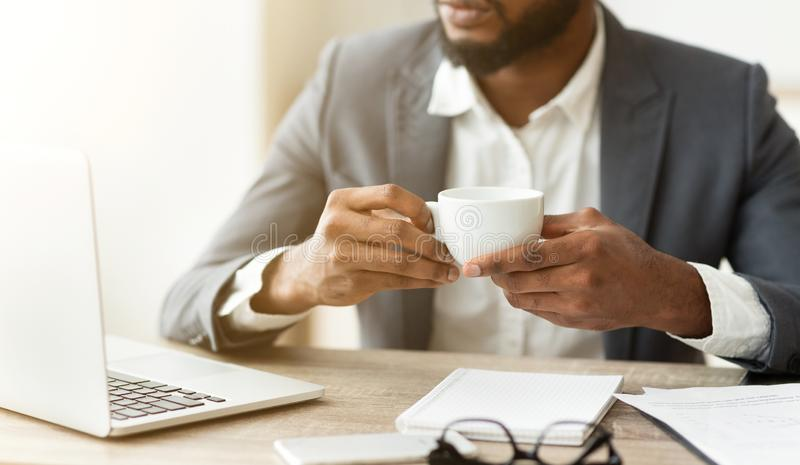Pensive businessman drinking coffee at workplace, thinking about new project. royalty free stock photos
