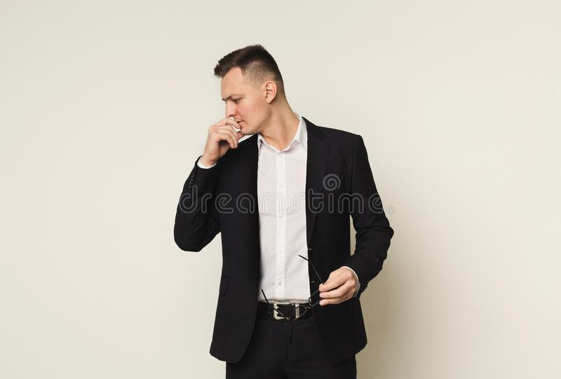 Pensive businessman with glasses in hand royalty free stock photos