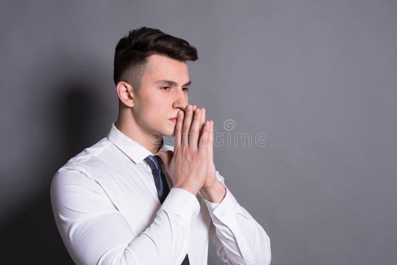 Pensive businessman at gray studio background stock photo
