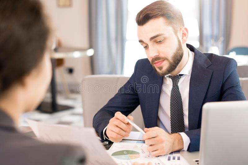 Pensive businessman listening to colleagues strategy. Serious pensive handsome businessman in suit listening to business offer from colleague and looking at stock images