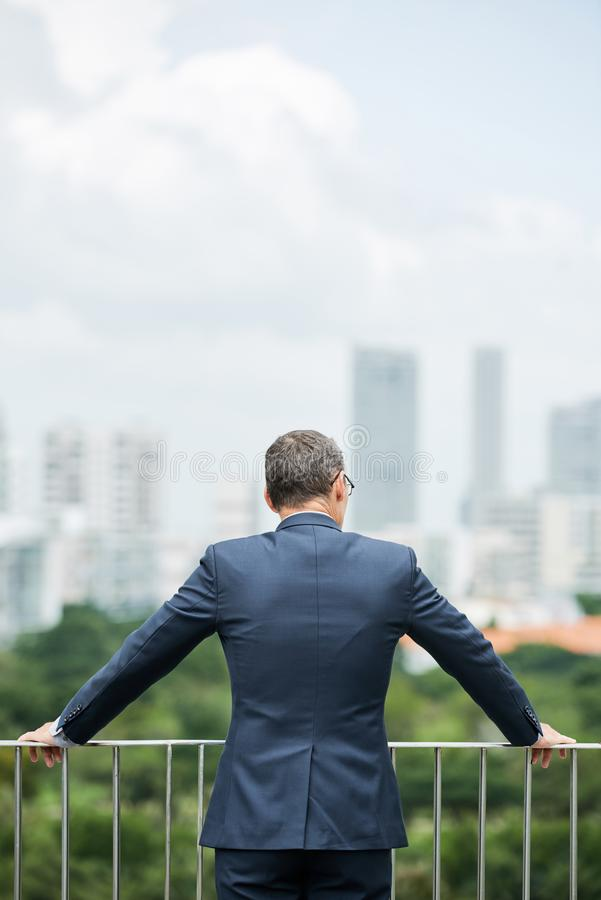 Conquering big city. Pensive businessman looking at city from the roof skyscraper stock photography