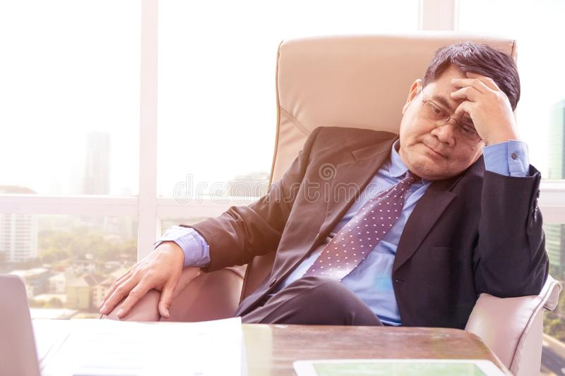 Pensive businessman sitting in the office royalty free stock photography