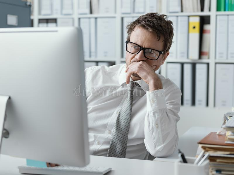Pensive businessman staring at the computer screen royalty free stock photos