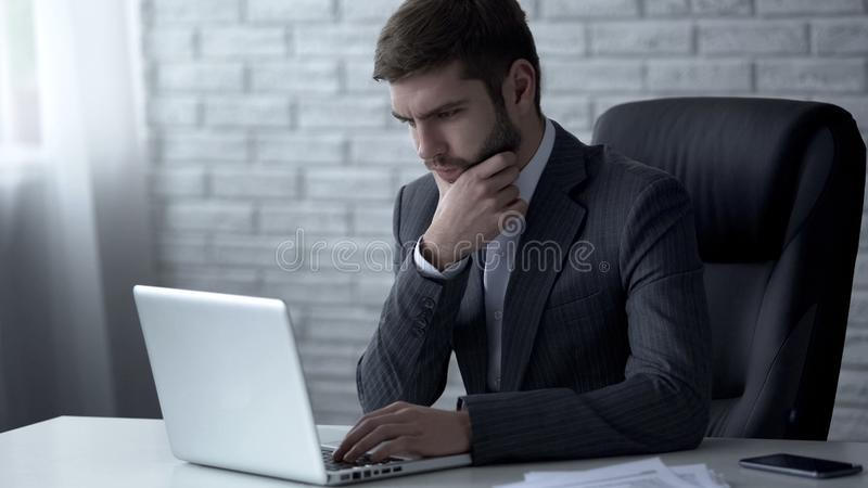 Pensive businessman typing on laptop, nervous about difficult startup solution royalty free stock photo