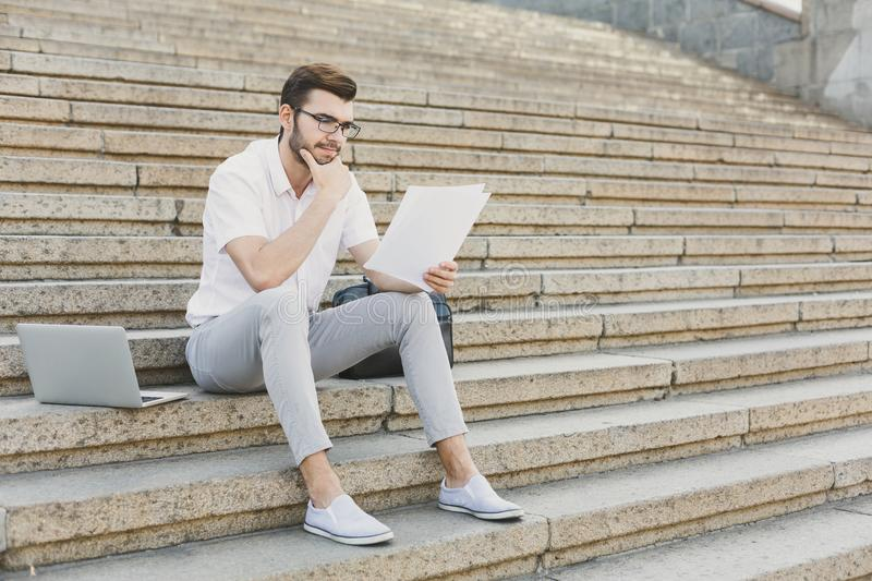 Pensive businessman working with papersoutdoors royalty free stock photos