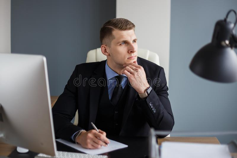 Pensive businessman at the workplace royalty free stock image