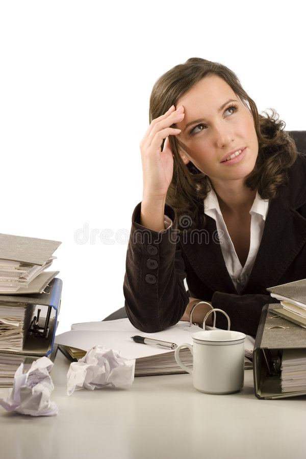 Pensive businesswoman. Sitting at a desk in an office stock photography