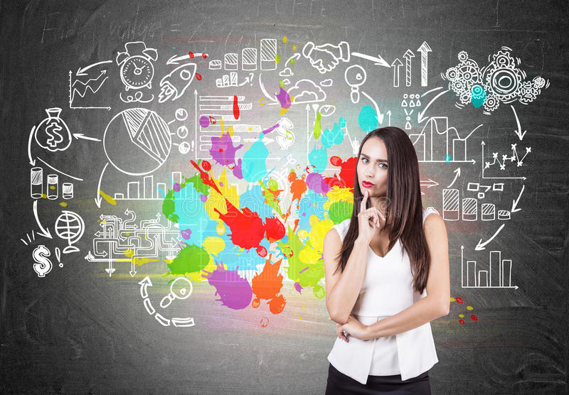 Pensive businesswoman, colorful business plan. Portrait of a pensive young businesswoman in a white and black suit. She is stnading near a blackboard with a stock photos