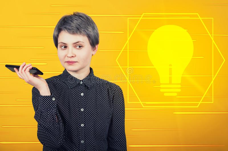 Pensive businesswoman holding mobile phone looking thinking of an innovative idea as light bulb symbol shining on yellow. Background. Modern technology stock photos