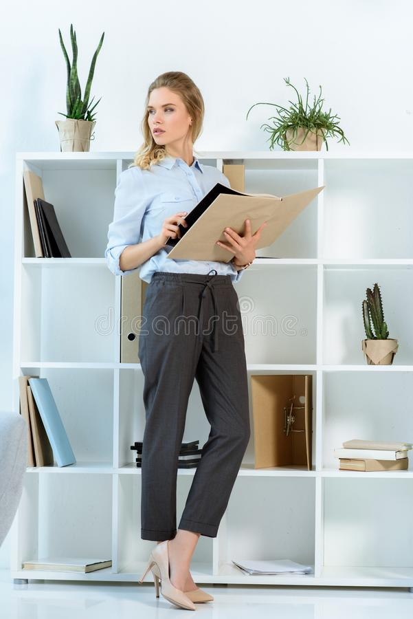 pensive businesswoman looking away while standing with work journal royalty free stock images