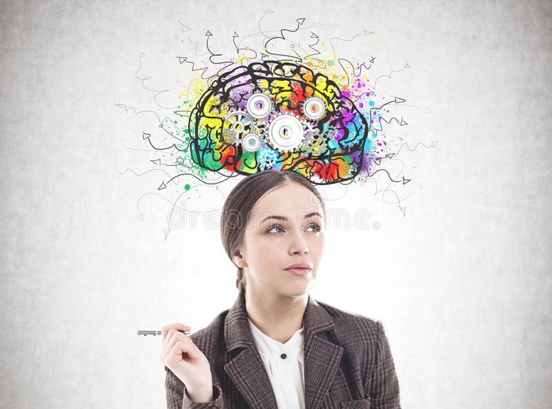 Pensive businesswoman with a pen, cog brain stock photography