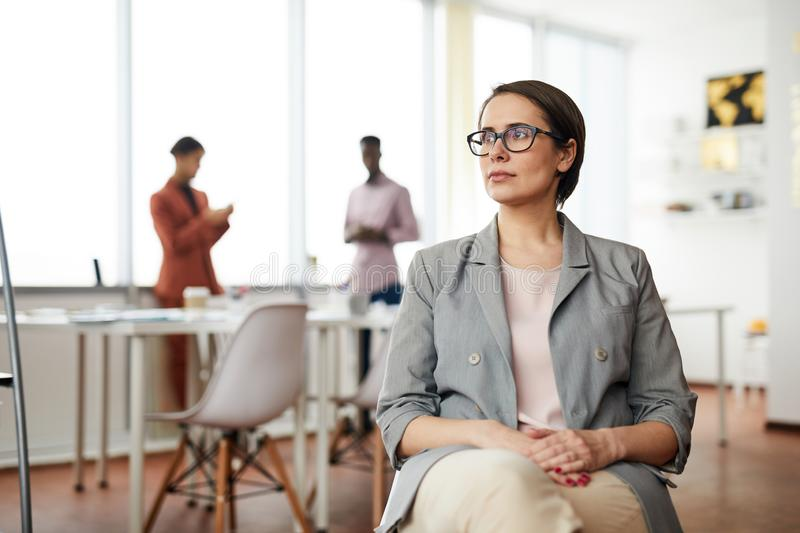 Pensive Businesswoman Sitting on Chair. Portrait of successful businesswoman sitting on chair in office and looking away pensively, copy space royalty free stock images