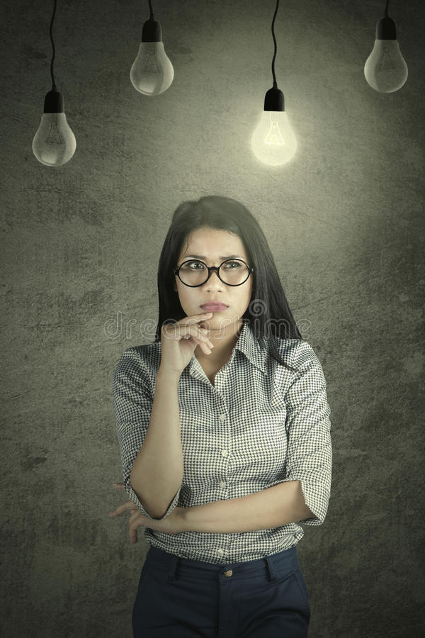 Pensive businesswoman under a bright bulb royalty free stock photo
