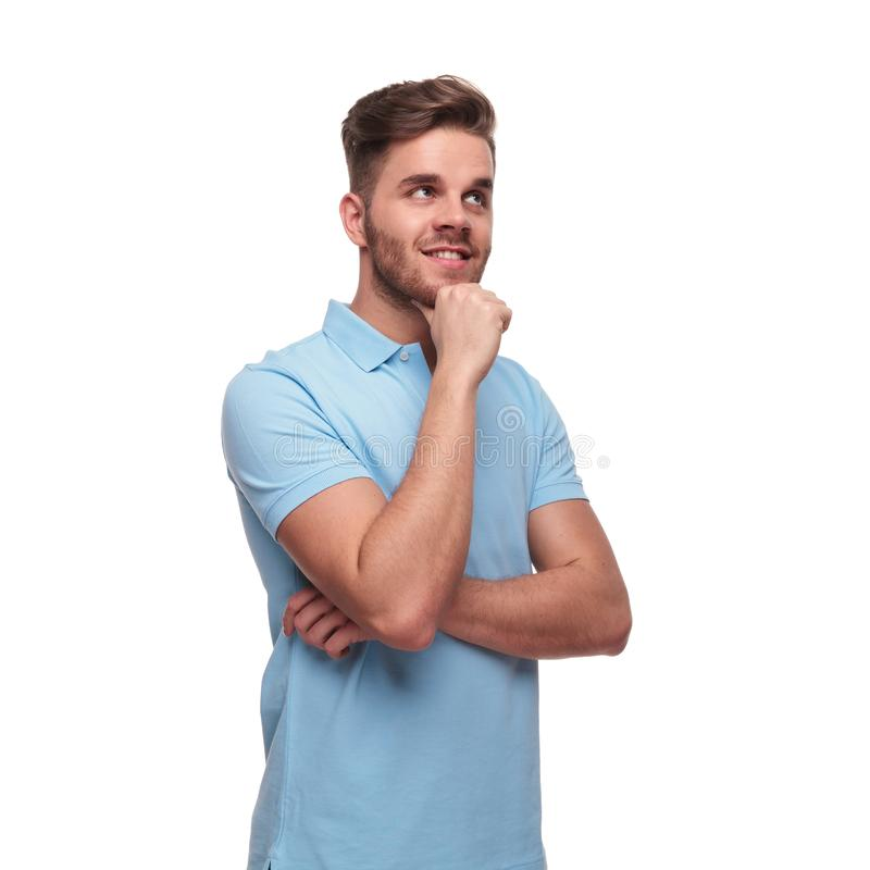 Pensive casual man wearing polo shirt looks up to side. Pensive casual man wearing blue polo shirt looks up to side while standing on white background, portrait royalty free stock photography
