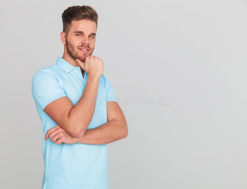 Pensive casual man wearing a polo shirt with short sleeves. Portrait of pensive young casual man wearing a light blue polo shirt with short sleeves while stock image