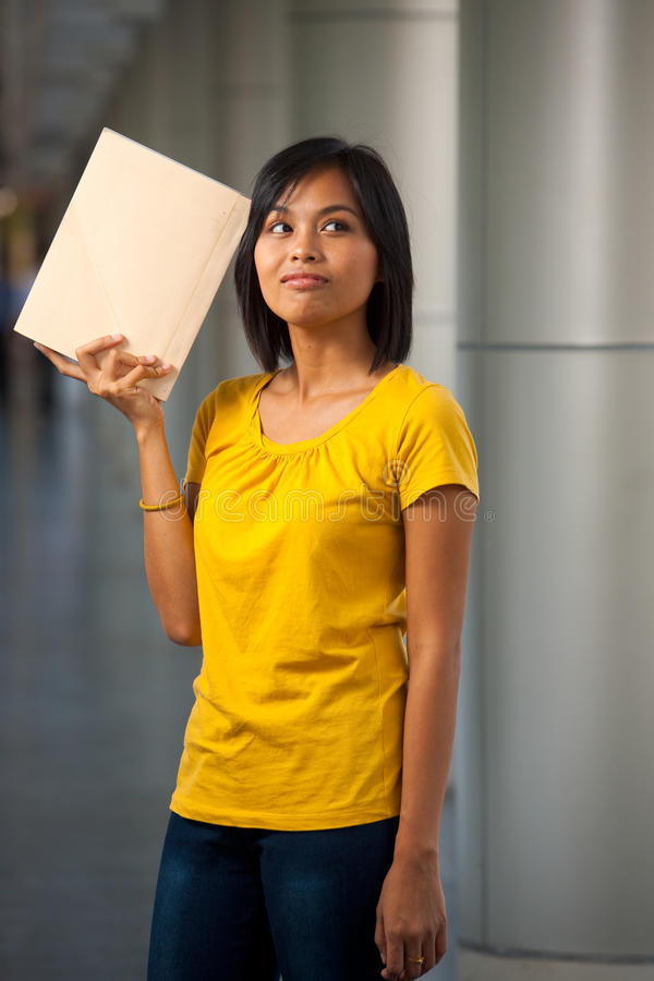 Pensive College Student Book Held High. A portrait of a cute college student thinking with a book against her head on a modern university campus. Young female stock photo