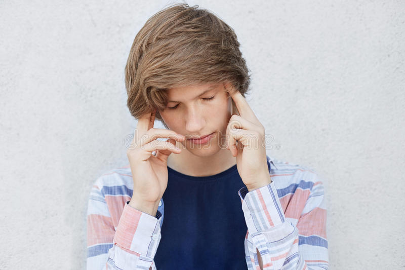 Pensive concentrated teenage boy with stylish haircut looking down thinking over something important. Fashionable male holding fin royalty free stock photos