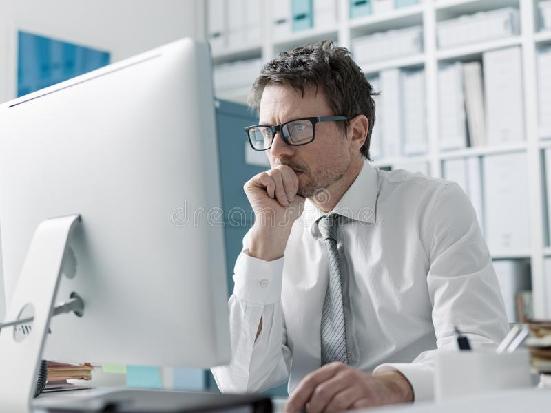 Pensive corporate executive working with a computer stock photos
