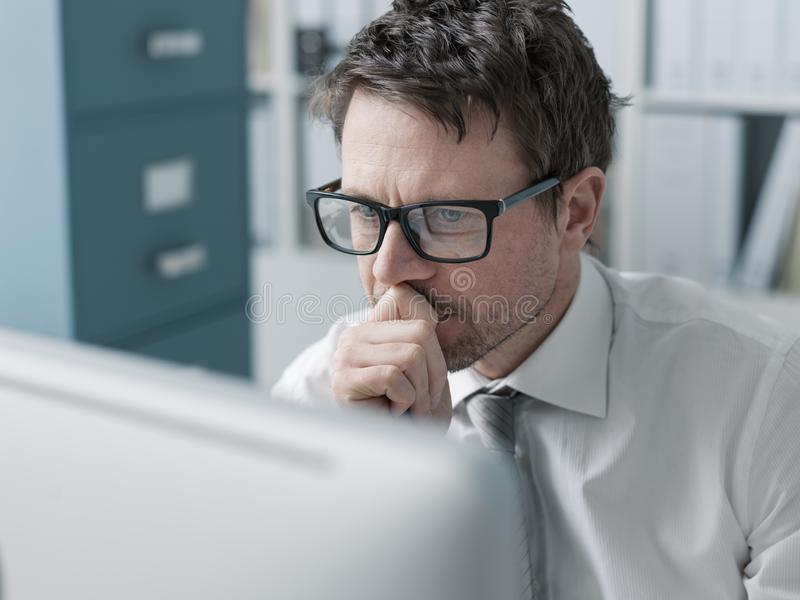 Pensive corporate executive working with a computer stock images