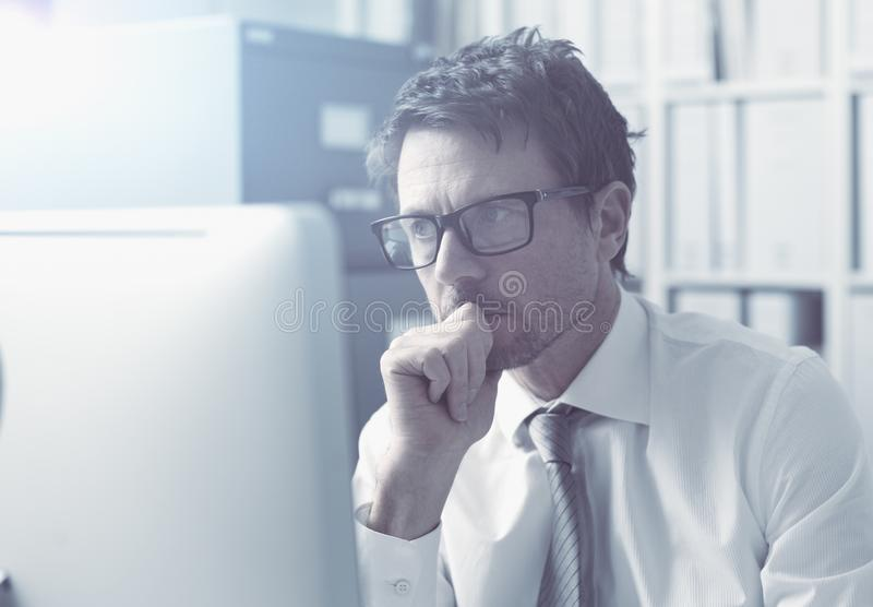 Pensive corporate executive working with a computer stock photo