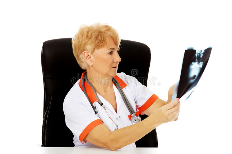 Pensive elderly female doctor looking for x-ray photo.  stock photos