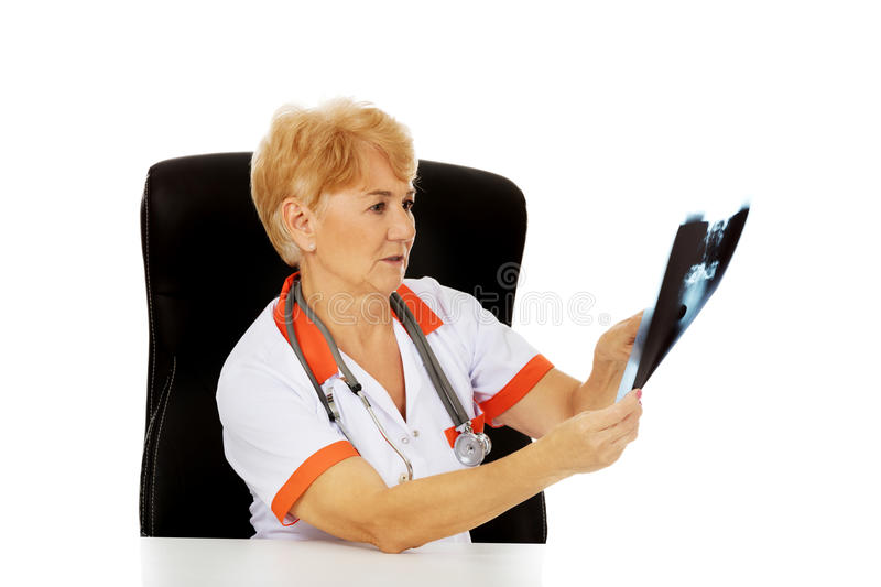 Pensive elderly female doctor looking for x-ray photo.  royalty free stock photography