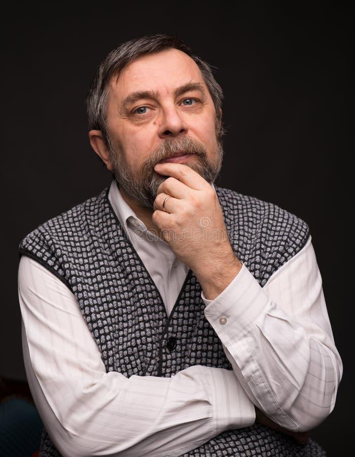 Pensive elderly man. On a dark background stock photography