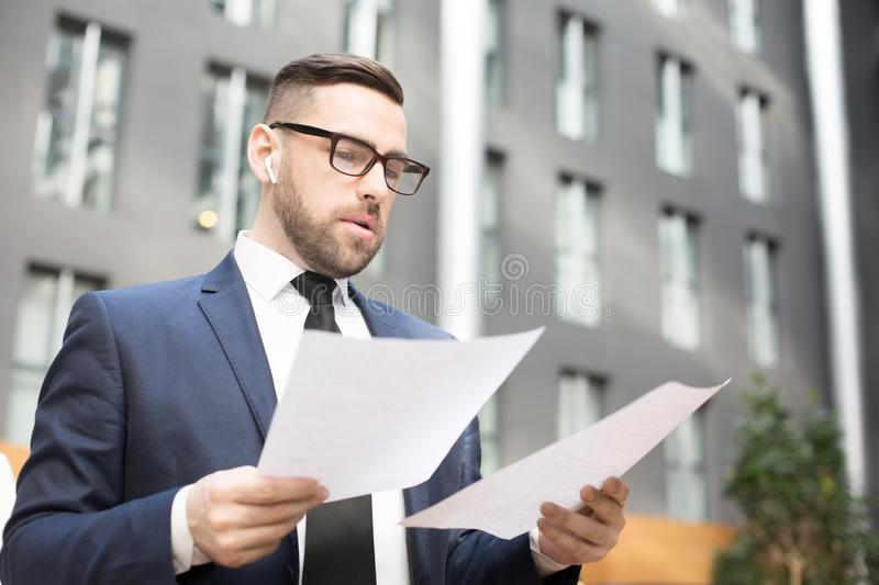 Pensive elegant man exploring papers outdoors royalty free stock images