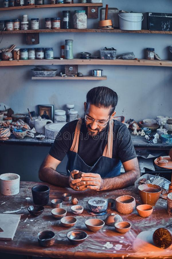 Pensive potter in glasses at his own workshop is workig on a new handmade teapot. Pensive entusiastici potter in glasses at his  own workshop is workig on a new stock image