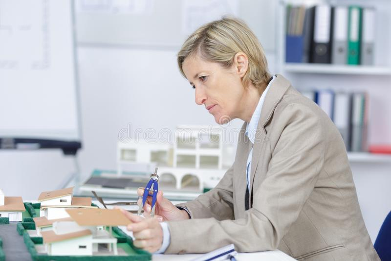 Pensive experienced female architect at work in office stock image
