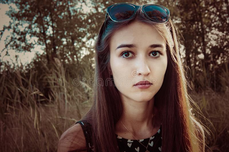Pensive face of a girl in nature stock photo