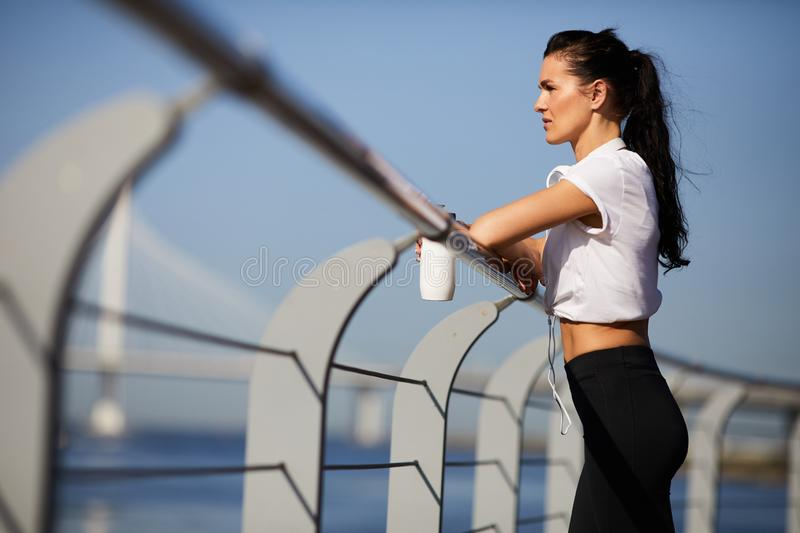 Pensive female athlete leaning on railing outdoors royalty free stock photos