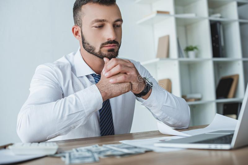 pensive financier sitting at table in office and looking royalty free stock photos