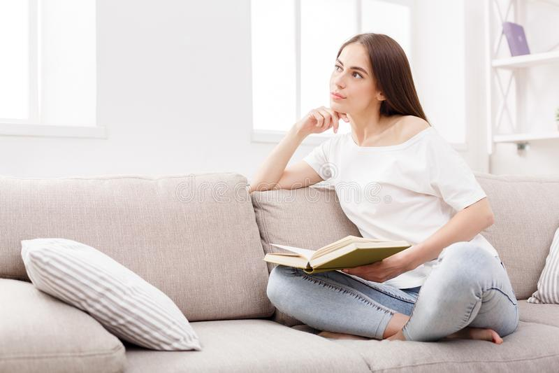 Young brunette woman reading the book at home on the couch. royalty free stock images