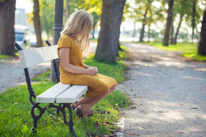 Pensive girl child alone in park royalty free stock photography