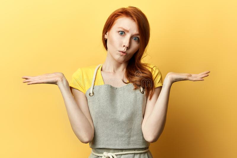 Pensive girl in gray apron doesn`t know the answer of the question royalty free stock images