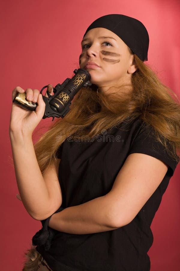 Pensive girl in pirate costume. Beautiful pensive girl in pirate costume with pistol in hand stock photo