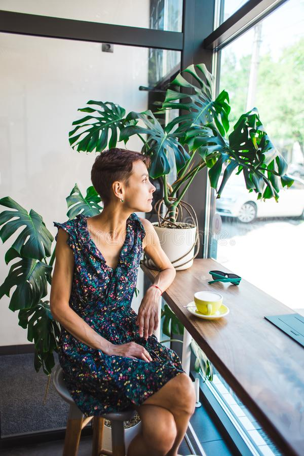 A woman with short hair dreamily looks out the window royalty free stock photos