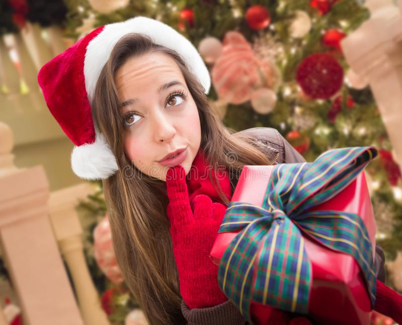 Pensive Girl Wearing A Christmas Santa Hat with Bow Wrapped Gif. Thinking Girl Wearing A Christmas Santa Hat with Bow Wrapped Gift In Front of Decorated Tree stock photo