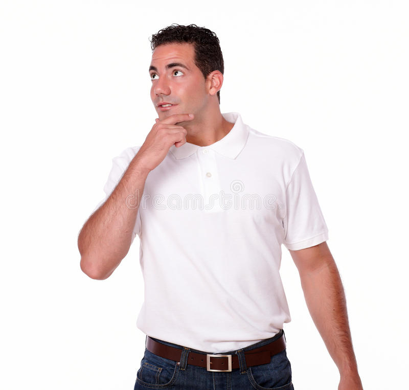 Pensive gorgeous guy looking at people. Portrait of a pensive gorgeous guy on white t-shirt looking at people while standing on isolated background - copyspace stock photos