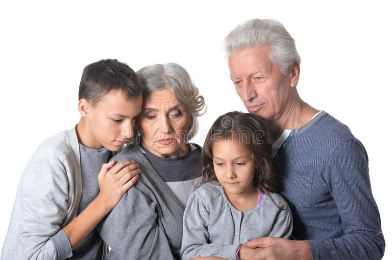 Pensive grandparents with kids. Portrait of pensive grandparents with kids isolated on white background royalty free stock photography