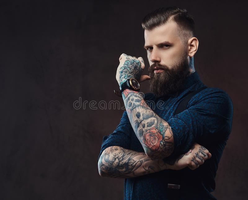 Pensive handsome old-fashioned hipster in a blue shirt and suspenders, standing with hand on chin in a studio. royalty free stock image