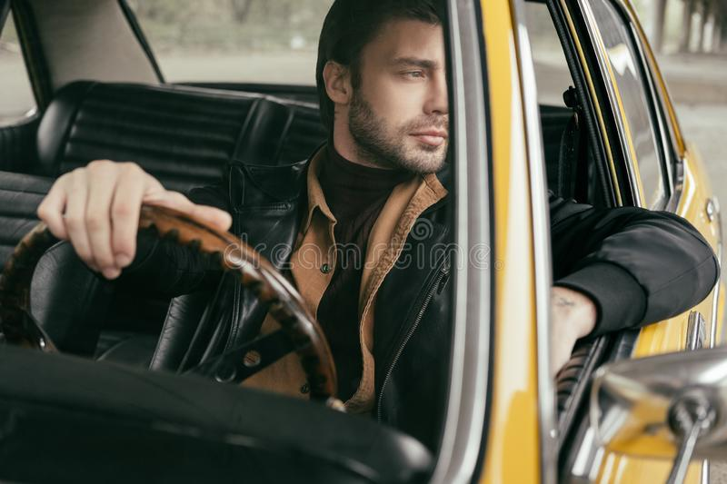 pensive handsome stylish man sitting in retro car and looking royalty free stock images