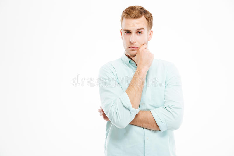 Pensive handsome young businessman stading with hands folded and thinking stock image