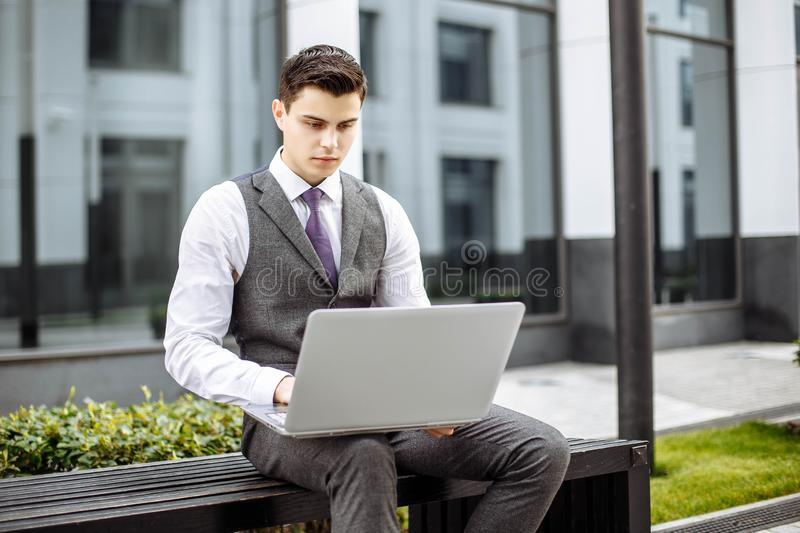 Pensive handsome young businessman using laptop in the city stock photo