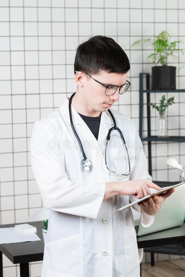 Pensive handsome young male doctor using tablet computer. Technologies in medicine concept royalty free stock photography