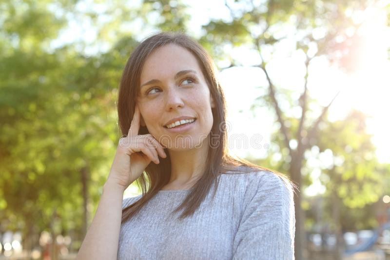 Pensive adult woman looking at side in a park stock images