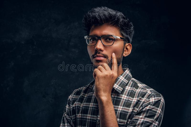 Pensive Indian student wearing eyewear and a plaid shirt. Studio photo against a dark textured wall royalty free stock images