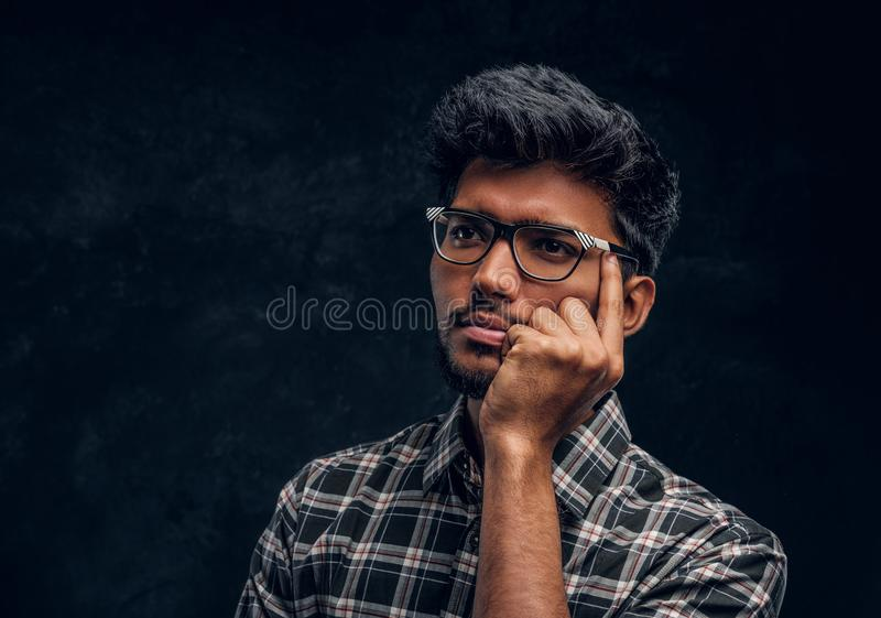 Pensive Indian student wearing eyewear and a plaid shirt. Studio photo against a dark textured wall stock photography