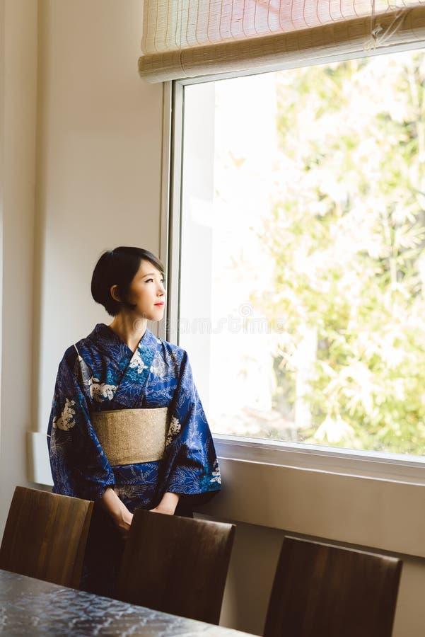 Pensive Japanese woman. In kimono looking through the window royalty free stock photo